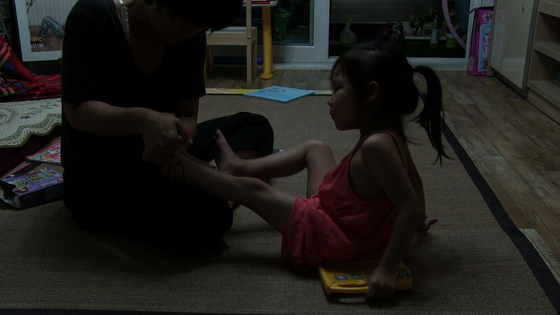 Kwon stretching Ji-hoo's feet in hopes of preventing her from walking on her tiptoes. [CINEMADAL]