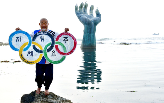"""Calligrapher Kim Dong-wook in a performance Tuesday in Homigot, North Gyeongsang, calls for Japan to revise the Tokyo Olympics map to exclude Korea's easternmost Dokdo islets. He wrote in another sign that """"Dokdo was protected with the lives of our ancestors."""" [NEWS1]"""