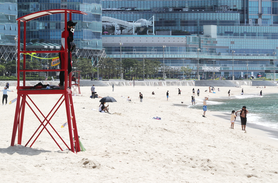 A lifeguard stands in a lookout tower at Haeundae Beach in Busan on Monday, after the beach pre-opened with quarantine measures taken amid the coronavirus pandemic. Haeundae and Songjeong beaches reopened on June 1, and no parasols or tubes will be provided during the month due to Covid-19. [YONHAP]
