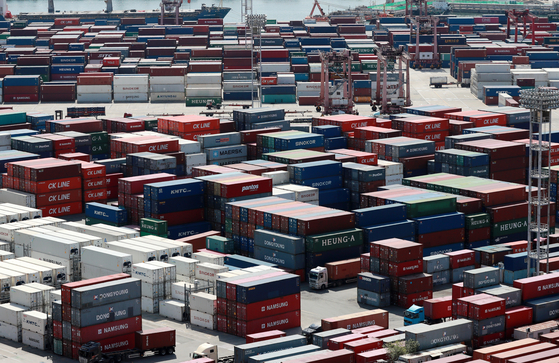 Cargo containers are stacked at a port in Busan on June 1. [YONHAP]