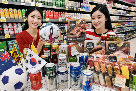 Models pose to promote a Homeplus sale celebrating the Korean football team's World Cup qualifying matches scheduled in June. The sale will run from Thursday to June 9, offering canned beer and popular anju, or snacks for drinkers, such as beef and jerky at discounted prices. [YONHAP]