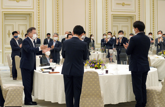 President Moon Jae-in, left, talks to the first-term lawmakers of the ruling Democratic Party at a Blue House meeting on Thursday. [YONHAP]