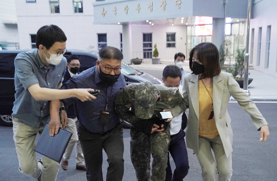 The sergeant accused of sexually harassing a female Air Force officer who later took her own life is escorted to his warrant review before a court martial in Gyeryong, South Chungcheong, on Wednesday. [YONHAP]