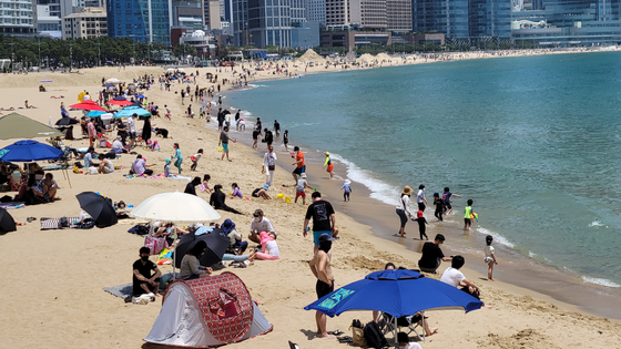 People enjoy the beach at Haeundae, Busan, on May 30 as the warm weather attracted beachgoers. Online travel, leisure and cultural purchases rose sharply in April. [YONHAP]