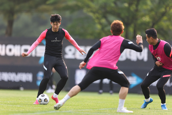 Son Heung-min, left, trains with the Korean football team at the National Football Training Center in Paju, Gyeonggi, on Monday. [YONHAP]