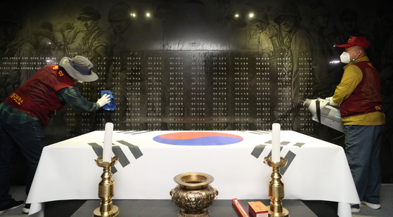 Workers disinfect the memorial monument in Suwon, Gyeonggi, on Thursday, so that visitors can safely pay their respects at the monument on Memorial Day on June 6. [NEWS1]