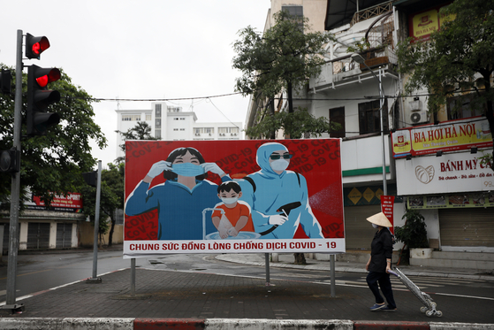 A woman walks past a sign about the Covid-19 pandemic in Hanoi, Vietnam, on April 23, 2020. Communist propaganda, which was most visible during the Vietnam War, has been revived in recent weeks as artists contribute to the national effort to fight the coronavirus. [EPA/LUONG THAI LINH/YONHAP]