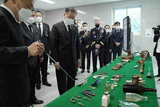 Heo Wook-gu. director of Ministry of National Defense Agency for KIA (Killed in Action) Recovery and Identification, far left, explains to President Moon about the objects found with the remains of veterans of the Korean War, at a center dedicated to the recovery of remains at the Seoul National Cemetery on Sunday. [YONHAP]