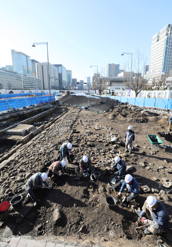 Workers holding 'homi,' a traditional Korean hoe, carefully excavate buried cultural properties discovered at the construction site of the new Gwanghwamun Plaza on March 22. [NEWS1]