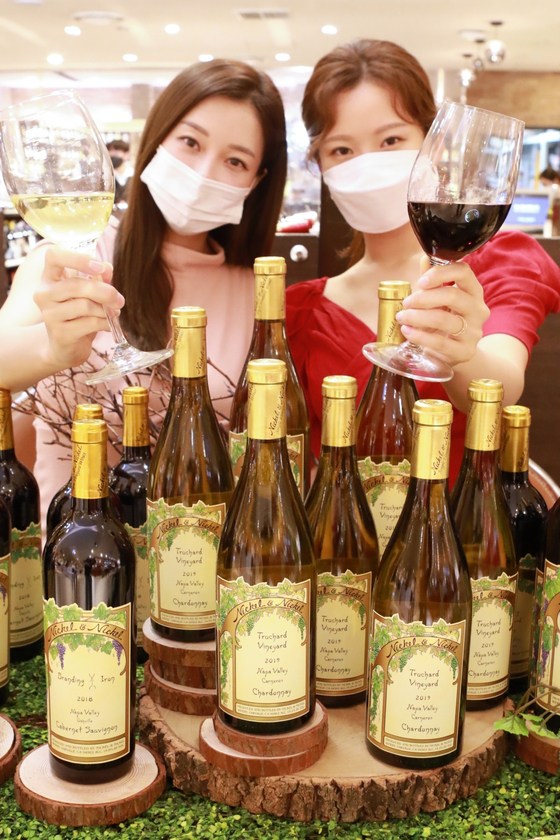 Models pose with four types of Nickel & Nickel wine at Lotte Department Store's main branch in central Seoul on Sunday. Nickel & Nickel is a single vineyard winery under Far Niente, a premium winery located in Napa Valley, California. [LOTTE DEPARTMENT STORE]