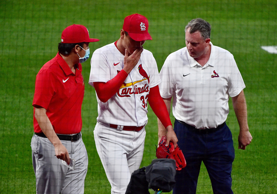 St. Louis Cardinals starting pitcher Kim Kwang-hyun walks off the field with a trainer prior to the start of the fourth inning against the Cincinnati Reds at Busch Stadium on Friday. [USA TODAY/YONHAP]