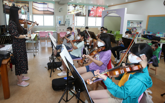 Elementary students learn how to play the violin in an after-school class at Mandeok Elementary School in Damyang, South Jeolla, on Monday. All students at 822 elementary and secondary schools in South Jeolla were required to come to school in person as the vaccination rate among its population exceeded 26 percent. [YONHAP]