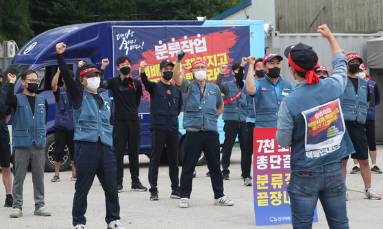 Members of Taekbae Union, which represents delivery workers, protest in front of a logistics center in Yongin, Gyeonggi, on Monday. Members are demanding companies to allow delivery workers to start their work at 9 a.m. in the morning and start delivery at 11 a.m. [NEWS1]
