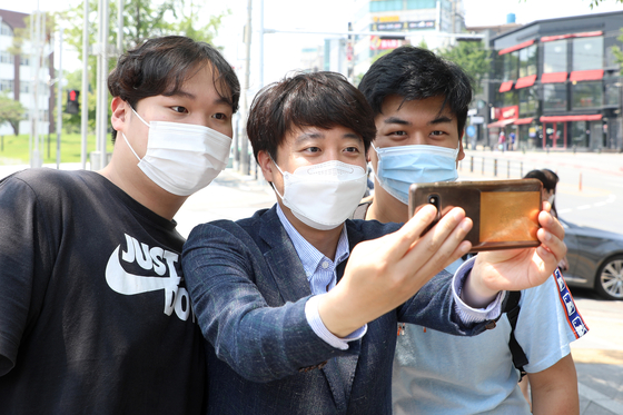 In this file photo, Lee Jun-seok, frontrunner of the People Power Party's chairmanship race, center, takes a photo with university students of Kyungpook National University in Daegu on May 24. [NEWS1]