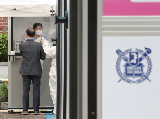 A faculty member from Seoul National University gets tested for Covid-19 at a rapid molecular testing center on campus on June 1. After expanding molecular Covid testing to all school members, Seoul National University plans to resume in-person classes this fall semester. [NEWS1]