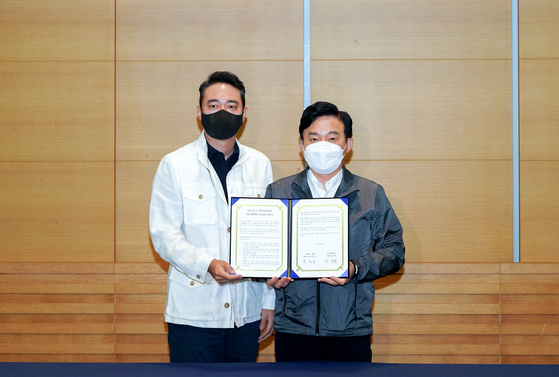 JoongAng Ilbo and JTBC CEO Hong Jeong-do, left, and Jeju Gov. Woon Hee-ryong pose for a photo to celebrate signing a memorandum of understanding at Pheonix Jeju in Seopjikoji, Jeju Island, on Monday. Based on the partnership, JoongAng Group will provide a kit that includes a biodegradable waste bag and gloves to Pheonix Jeju visitors, encouraging guests to help pick up ocean waste. [YONHAP]