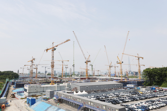 Tower cranes suspended at a construction site in Seoul on Tuesday. Tower crane operators have gone on strike, demanding stricter monitoring of unmanned cranes by the government. The government recently revoked licenses for 120 unmanned cranes but workers say these cranes are still used in the field. The tower crane operators first held a strike on the issue in June 2019. [YONHAP]
