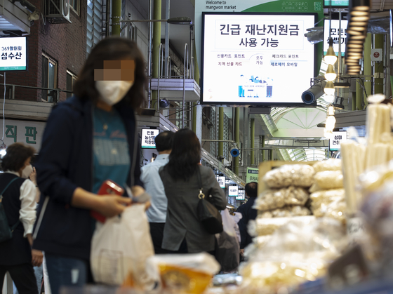 A board at the Mangwon traditional market in May 2020 advertises that stores accept emergency relief grants. The Democratic Party is pushing to include a similar grant for every Korean household in the second supplementary budget this year. [YONHAP]