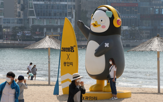 Visitors take photos with a statute of maskless Pengsoo, a popular penguin character created by the national education broadcasting channel EBS, at Gwangalli Beach in Busan on Tuesday. Last year, Pengsoo itself wore a mask to symbolize preventing the spread of Covid-19, but this year, Pengsoo took off its mask and now sports a bandage on its arm from being vaccinated, encouraging more people to take part in the vaccination campaign. [SONG BONG-GEUN]