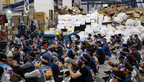Delivery workers in Korea stage a demonstration at a logistics center in Songpa District in southern Seoul Wednesday as negotiations on improving working conditions fell through. Some 2,000 workers launched a full-fledged walkout Wednesday after 92 percent of 5,823 union members voted for the strike. [YONHAP]