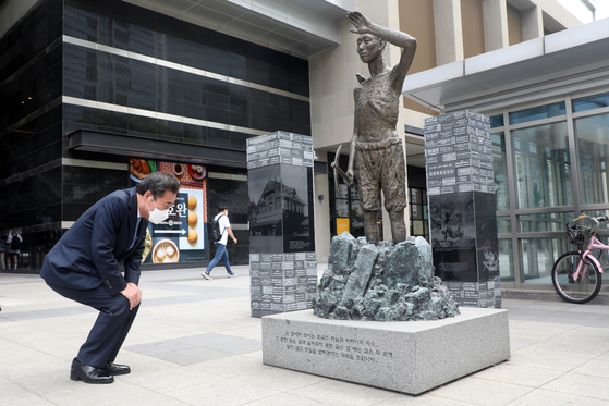 Lee Nak-yeon, a former prime minister and former head of the Democratic Party, observes a statue representing a conscripted worker during Japanese occupation in front of Yongsan Station, central Seoul, on Wednesday — two days after a Seoul court dismissed a case on forced labor victims. He met with forced labor victims earlier that day. [NEWS1]