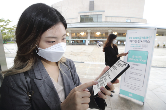 A visitor to Seoul Arts Center uses KT's Call Check-in service via her smartphone in Seocho District, southern Seoul, on June 7. [YONHAP]