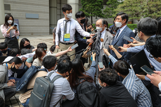 Lim Chul-ho, center, the son of a deceased forced laborer, speaks to reporters Monday afternoon about plans to appeal after the Seoul Central District Court dismissed a lawsuit by 85 Korean victims of wartime forced labor and their families against 16 Japanese companies, the largest of its kind. [YONHAP]