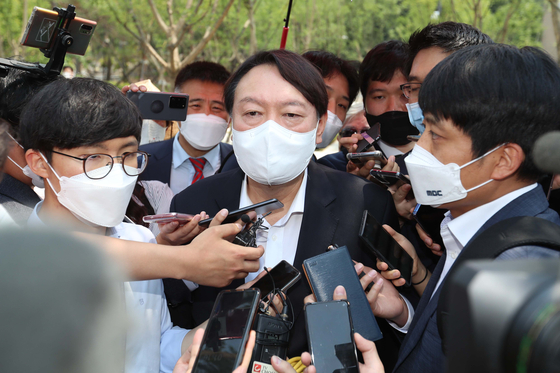 Former Prosecutor General Yoon Seok-youl is asked questions by reporters as he makes his way to the opening of the Woodang Memorial Hall in central Seoul on Wednesday. [YONHAP]