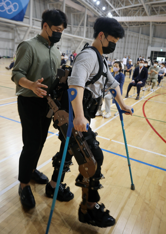 A visitor tries a wearable robot for the disabled during an event at Gangneung Yeongdong University in Gangneung, Gangwon, on Wednesday. The testing of the robot will take place between June and September at the university's physiotherapy simulation center. [YONHAP]
