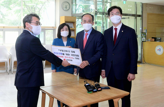 Representatives of the People Power Party (PPP), from left to right, Jun Joo-hyae, Choo Kyung-ho and Kang Min-kuk, submit their party's request to the Board of Audit and Inspections in Jongro District, central Seoul, on Wednesday for an audit of party members' real estate matters. [OH JONG-TAEK]