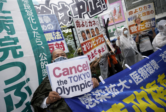 Protesters in Japan hold banners during a rally against the coming Tokyo Olympics Sunday, as the Japanese capital is still in a state of emergency and locals fear a further spread of Covid-19 with the arrival of thousands of athletes and staff from overseas. [EPA/YONHAP]