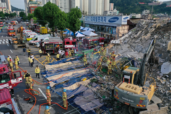 A five-story building being demolished in Gwangju collapsed suddenly on Wednesday afternoon, inundating a public bus that was stopped in front of it. Twelve passengers were aboard the bus and eight were rescued by 7:17 p.m. Two passengers were confirmed dead. [YONHAP]