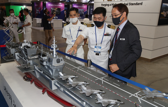 Visitors look at a miniature of a light aircraft carrier on display at the International Maritime Defense Industry Exhibition (Madex) in Busan on Wednesday. Some 120 companies from seven countries are participating in the exhibition. [NEWS1]
