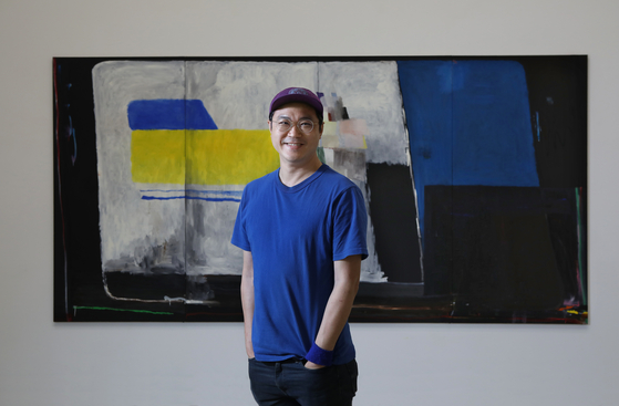 """Bek Hyun-jin poses for a photo after an interview with the Korea JoongAng Daily in front of his work """"Bright Darkness"""" (2020) at PKM Gallery in central Seoul Wednesday. [PARK SANG-MOON]"""