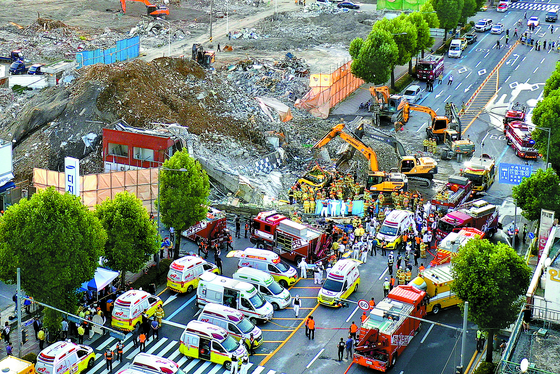 Firefighters work to remove the remains of a five-story building that collapsed on a city bus in Gwanjgu Wednesday afternoon. At least nine were killed and eight seriously injured in the accident.  [CHUNG JEONG-PIL]