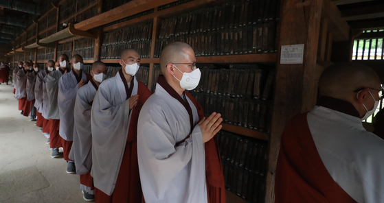 Monks look around printing woodblocks of Tripitaka Koreana (also called Palman Daejanggyeong) preserved in Haein Temple in Hapcheon, South Gyeongsang, on Thursday. The temple will allow the general public to appreciate the cultural asset, National Treasure 32, in person on Saturdays and Sundays starting from June 19. The Buddhist scriptures were carved on over 80,000 blocks of wood in the 13th century. The Tripitaka Koreana was registered in 2007 on Unesco's world heritage list. [YONHAP]
