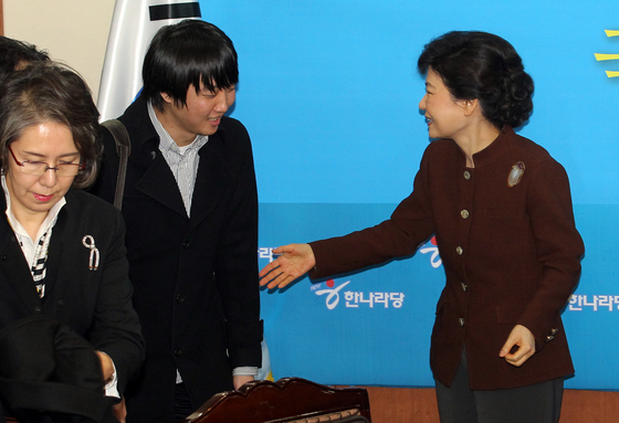 In this file photo, Park Geun-hye, then acting leader of the Grand National Party, right, talks to Lee Jun-seok, a member of the acting leadership, in December 2011.