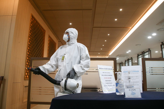 A sanitization worker disinfects the main building of the National Assembly on Friday after the legislature was temporarily shut due to four Democratic Party members testing positive. [YONHAP]