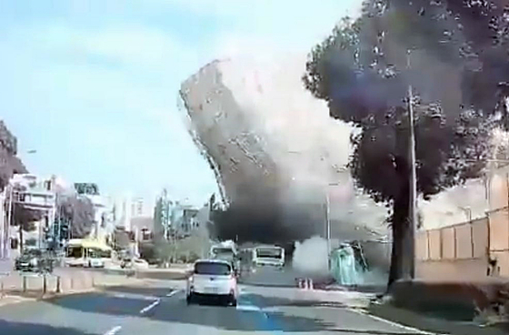 In this image from a car's black box, a five-story building collapses during demolition and falls on a bus in Gwangju on Wednesday.  [NEWS1]