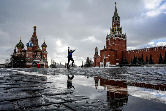 A man gestures as he walks along the Red Square in front of the Saint Basil cathedral and Spasskaya tower in Moscow on March 8. [YURI KADOBNOV/AFP/YONHAP]