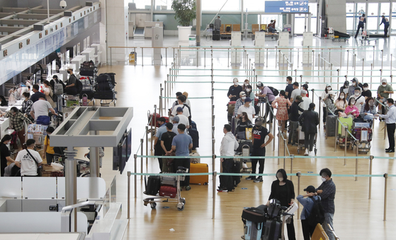 People line up to travel abroad at Incheon International Airport on Friday afternoon. [NEWS1]