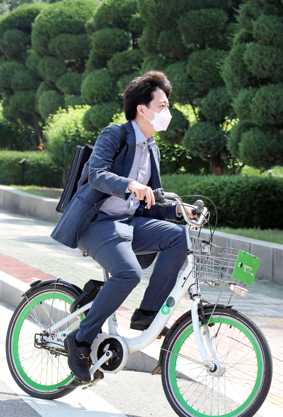 People Power Party Chairman Lee Jun-seok rides a city rental bicycle, commongly known as a ddareungi, on his commute to the National Assembly on Sunday. [OH JONG-TAEK]