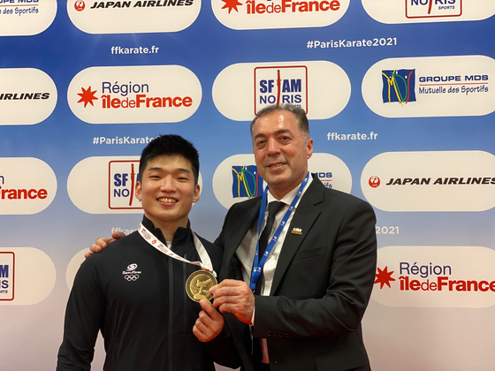 Park Hee-jun holds his bronze medal with his coach Ahmad Safi, after finishing third in the men's Kata at the 2020 Olympic Qualification Tournament in Paris on Saturday.  [Korea Karate Federation]