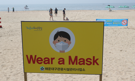 After a group of foreigners enjoyed fireworks at Haeundae beach without wearing face masks last year, an English sign was set up requesting people to wear masks. [SONG BONG-GEUN]