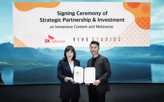 SK Telecom's head of metaverse Jeon Jin-soo (left) and Vive Studios CEO Kim Se-kyu pose after signing a strategic partnership around immersive content on Monday. SK Telecom has also acquired part of Vive Studios. [YONHAP]