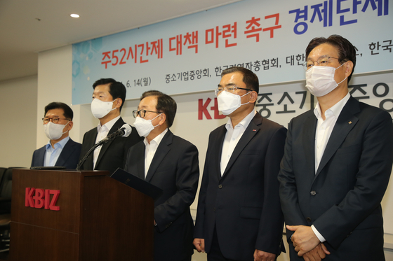 Representatives of five business lobbying groups call for the postponement of the 52-hour workweek for small companies on Monday at the office of KBIZ in Yeouido, western Seoul. [KBIZ]