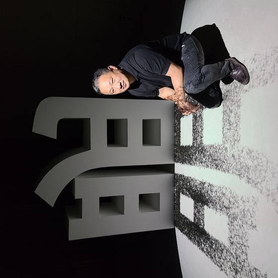 Artist Lee Lee-nam poses in front of his installation artwork ″Reversed Light,″ which shows the Chinese character myeong (light) and its shadow moving in the direction of the light, instead of the opposite way, which is how it's supposed to move. [SAVINA MUSEUM]