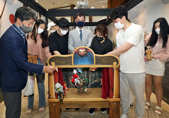 Czech Ambassador to Korea Gustav Slamecka, center, professor Kim In-chon of Czech and Slovak studies at Hankuk University of Foreign Studies, far left, and students majoring in Czech studies at the university try their hand at puppetry at the ″Secrets of Wooden Puppets: Czech Marionettes″ exhibition at the Seoul Museum of History in central Seoul on Thursday. [PARK SANG-MOON]