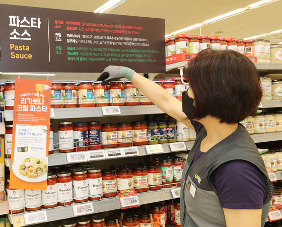 An employee displays pasta sauces at Emart's Seougsu branch in eastern Seoul. At Emart, some 100 different pasta sauces are available so far. [EMART]