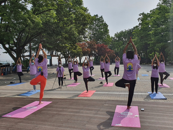 Sripriya Ranganathan, ambassador of India to Korea, center in the front row of people facing the instructors, and staff members at the embassy take part in a yoga session at Namsan Tower in central Seoul on Monday in the lead up to International Yoga Day on June 21. To celebrate the seventh year since the day was first dedicated to yoga by the United Nations, the Swami Vivekananda Cultural Centre of the Embassy of India in Seoul is organizing a number of yoga sessions in Seoul, Busan, Gimhae and other cities in partnership with local schools and universities. [EMBASSY OF INDIA TO KOREA]